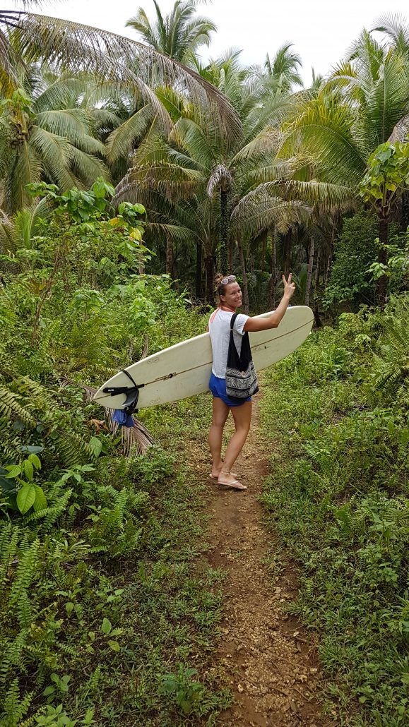 met surfplank door de jungle