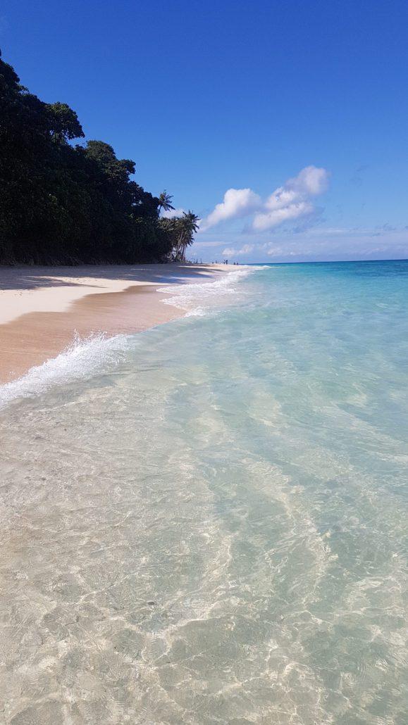 wit strand, blauw water en palmbomen