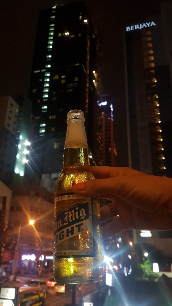 cheers with beer and big building makati